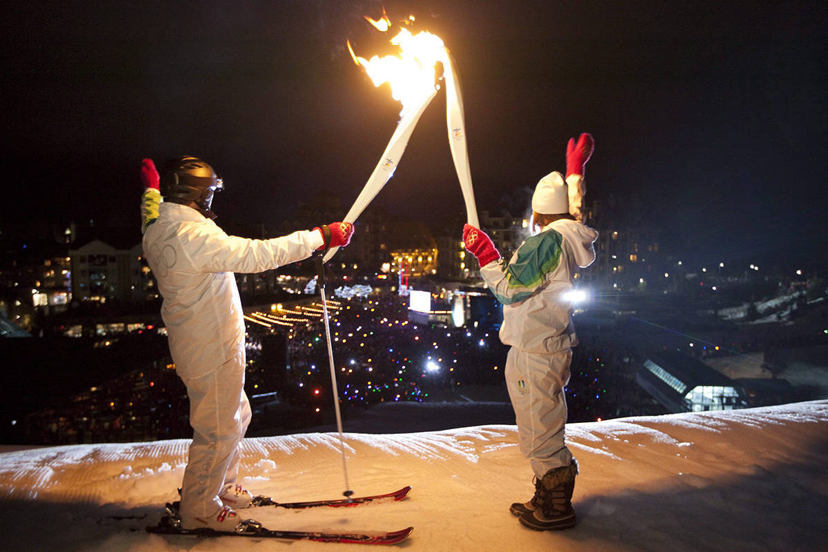 The Olympic flame is passed from skicross athlete Julia Murray to former World Cup and Olympic downhill ski racer Steve Podborski in Whistler, B.C. Friday, Feb. 5, 2010. The Olympic Flame which traveled all the way from Olympia in Greece is now on a 106 day cross country relay which will end in Vancouver on Feb. 12, 2010 to mark the start of the Vancouver 2010 Winter Olympic Games. THE CANADIAN PRESS/Jonathan Hayward