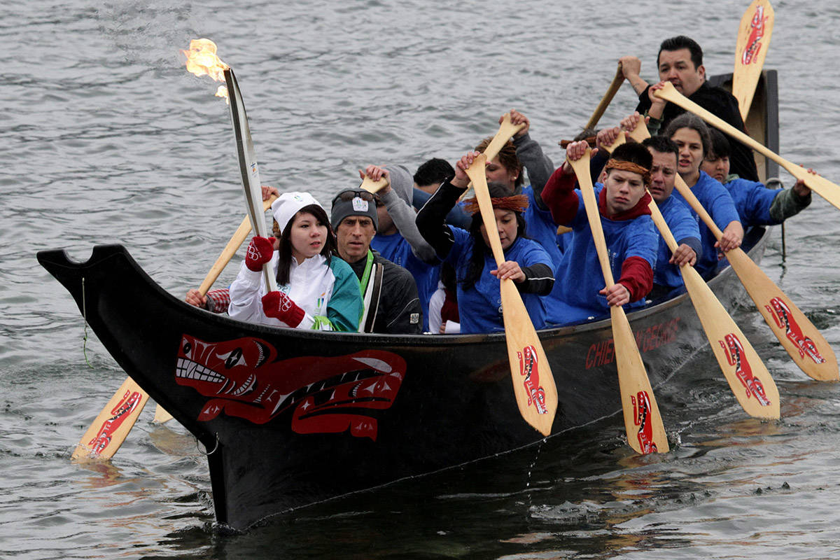 Ocean Hyland carries the Olympic flame on an Aboriginal canoe on the waters of Burrard Inlet at the Tsleil-Waututh First Nation during the Olympic torch relay in North Vancouver, B.C., on Wednesday February 10, 2010. The Olympic flame is on a 106 day journey across Canada in the longest domestic torch relay in Olympic history. It will end with the lighting of the Olympic cauldron at the opening ceremonies for the Vancouver Winter Olympics on February 12. THE CANADIAN PRESS/Darryl Dyck