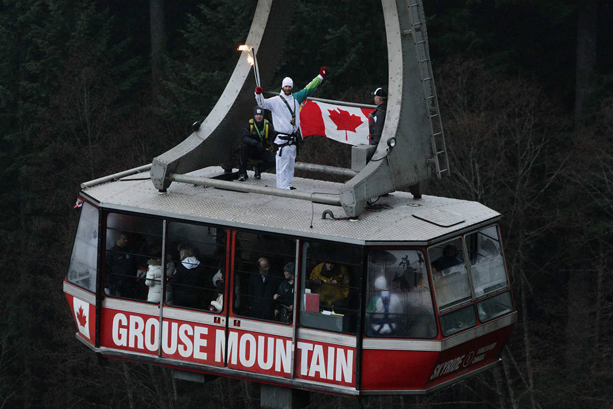 Canadian snowboarder Justin Lamoureux, of Squamish, B.C., carries the Olympic flame while riding on top of a cable car at Grouse Mountain in North Vancouver, B.C., on Wednesday February 10, 2010. The Olympic flame is on a 106 day journey across Canada in the longest domestic torch relay in Olympic history. It will end with the lighting of the Olympic cauldron at the opening ceremonies for the Vancouver Winter Olympics on February 12. THE CANADIAN PRESS/Darryl Dyck