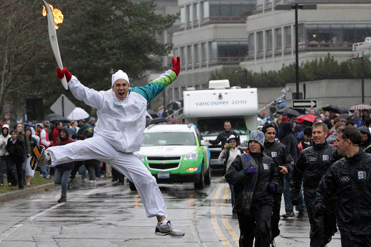 Torchbearer Michael Tchao jumps as he carries the Olympic flame during the Olympic torch relay at Simon Fraser University in Burnaby, B.C., on Thursday February 11, 2010. The Olympic flame is on a 106 day journey across Canada in the longest domestic torch relay in Olympic history. It will end with the lighting of the Olympic cauldron at the opening ceremonies for the Vancouver Winter Olympics on February 12. THE CANADIAN PRESS/Darryl Dyck