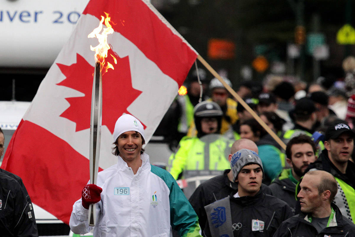 Phoenix Suns' Steve Nash, of Victoria, B.C., carries the Olympic flame during the Olympic torch relay in Vancouver, B.C., on Thursday February 11, 2010. The Olympic flame is on a 106 day journey across Canada in the longest domestic torch relay in Olympic history. It will end with the lighting of the Olympic cauldron at the opening ceremonies for the Vancouver Winter Olympics on February 12. THE CANADIAN PRESS/Darryl Dyck