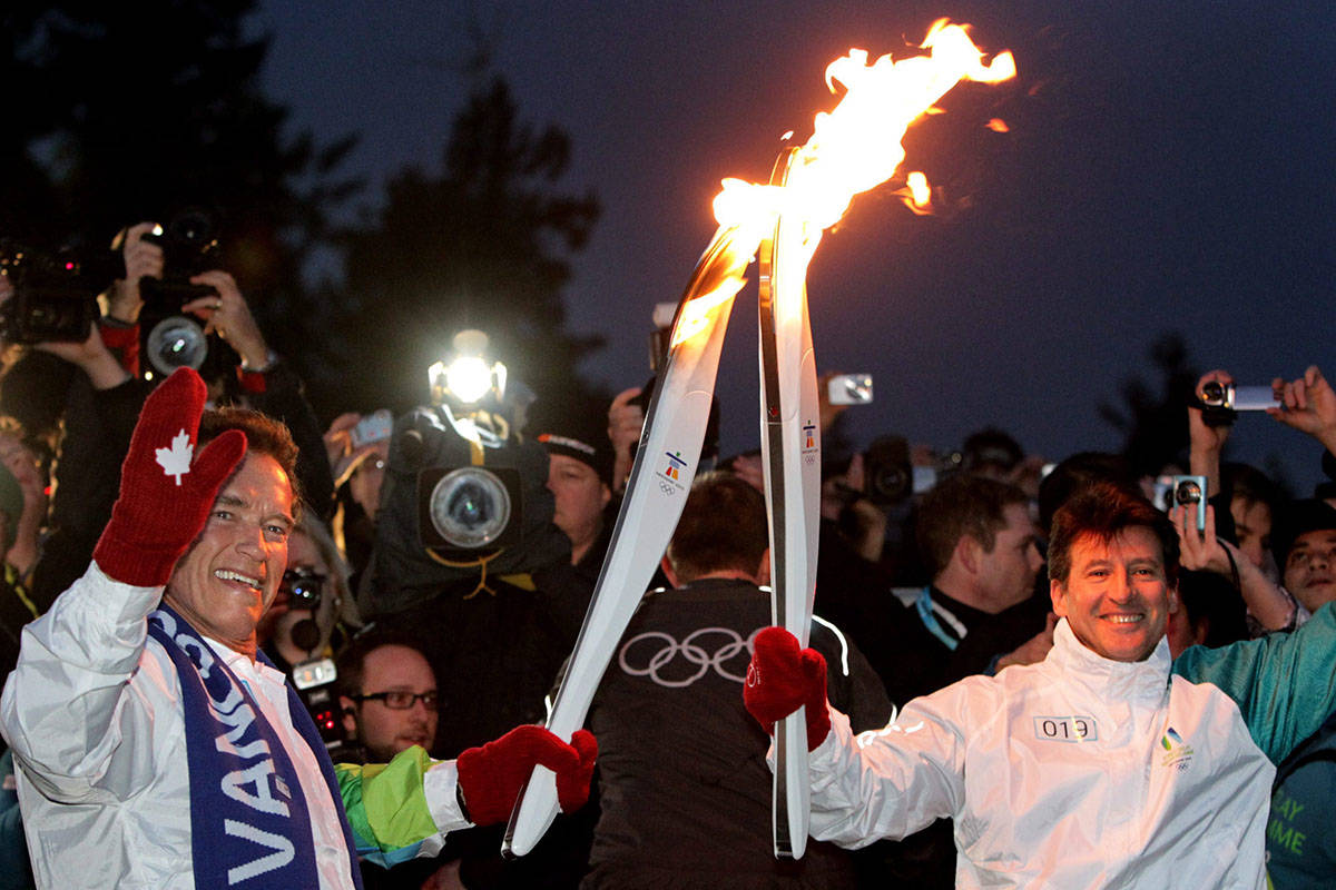 California Governor Arnold Schwarzenegger, left, passes the Olympic flame to Seb Coe, Chair of the London 2012 Olympic Organizing Committee and Olympic gold medalist, during the Olympic torch relay in Vancouver, B.C., on Friday February 12, 2010. The Olympic flame ends its 106-day journey across Canada today in the longest domestic torch relay in Olympic history. THE CANADIAN PRESS/Darryl Dyck