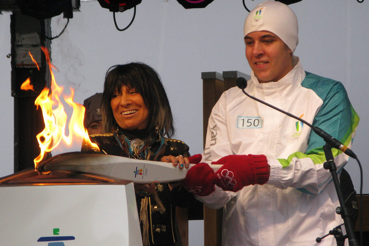 Singer songwriter Buffy Sainte-Marie, left, helps Malcolm Crawford with the Olympic torch on February 12, 2010 in Vancouver. Crawford carried the torch in the final leg before the Olympic opening ceremonies. THE CANADIAN PRESS/Bill Graveland