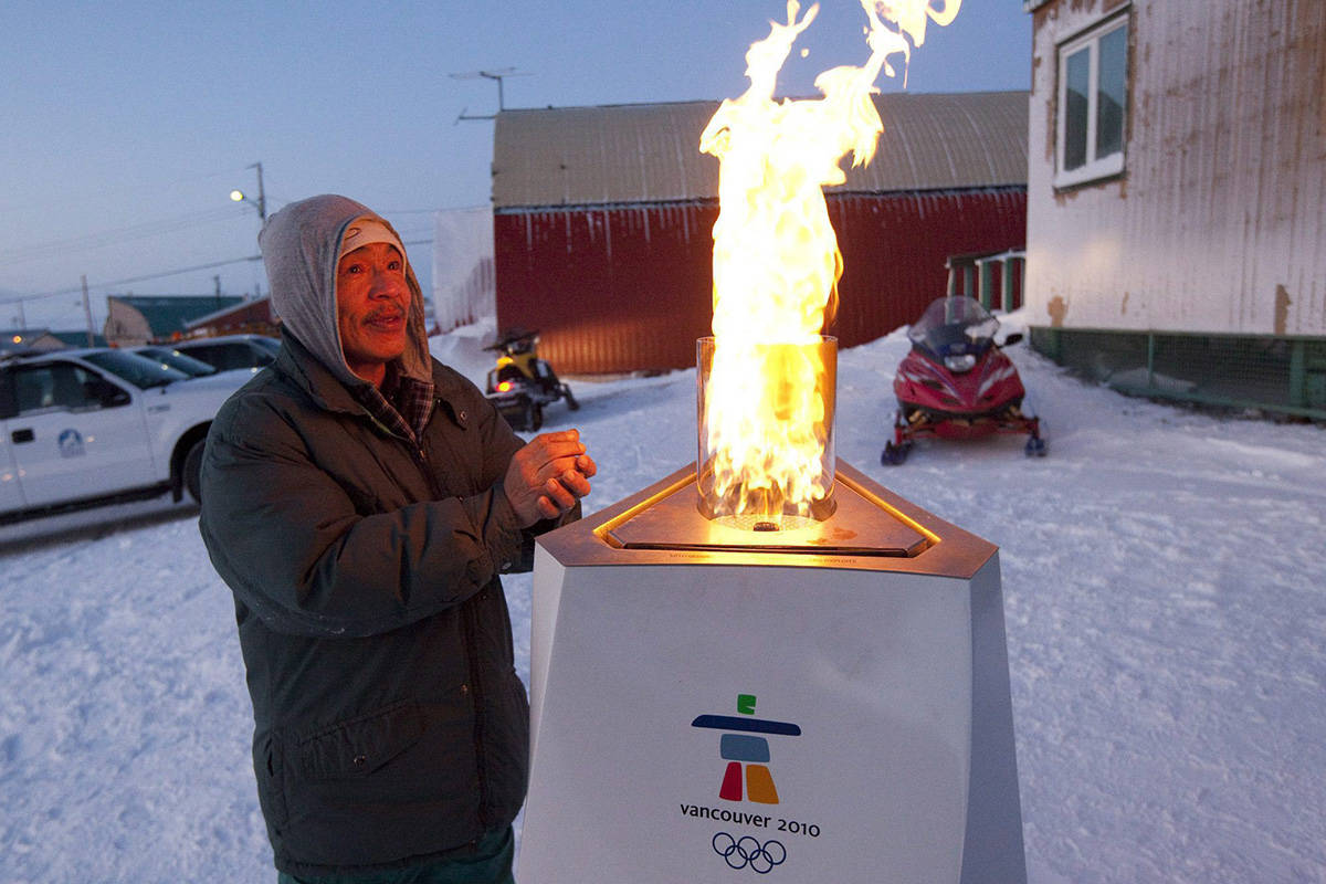 A native man warms his hands on the Olympic Flame as it burns in the community cauldron in Resolute Bay, Nunavut, Monday Nov. 9, 2009. The Olympic Flame which travelled all the way from Olympia in Greece is now on a 106 day cross country relay which will end in Vancouver on Feb. 12, 2010 to mark the start of the Vancouver 2010 Winter Olympic Games. THE CANADIAN PRESS/Jonathan Hayward