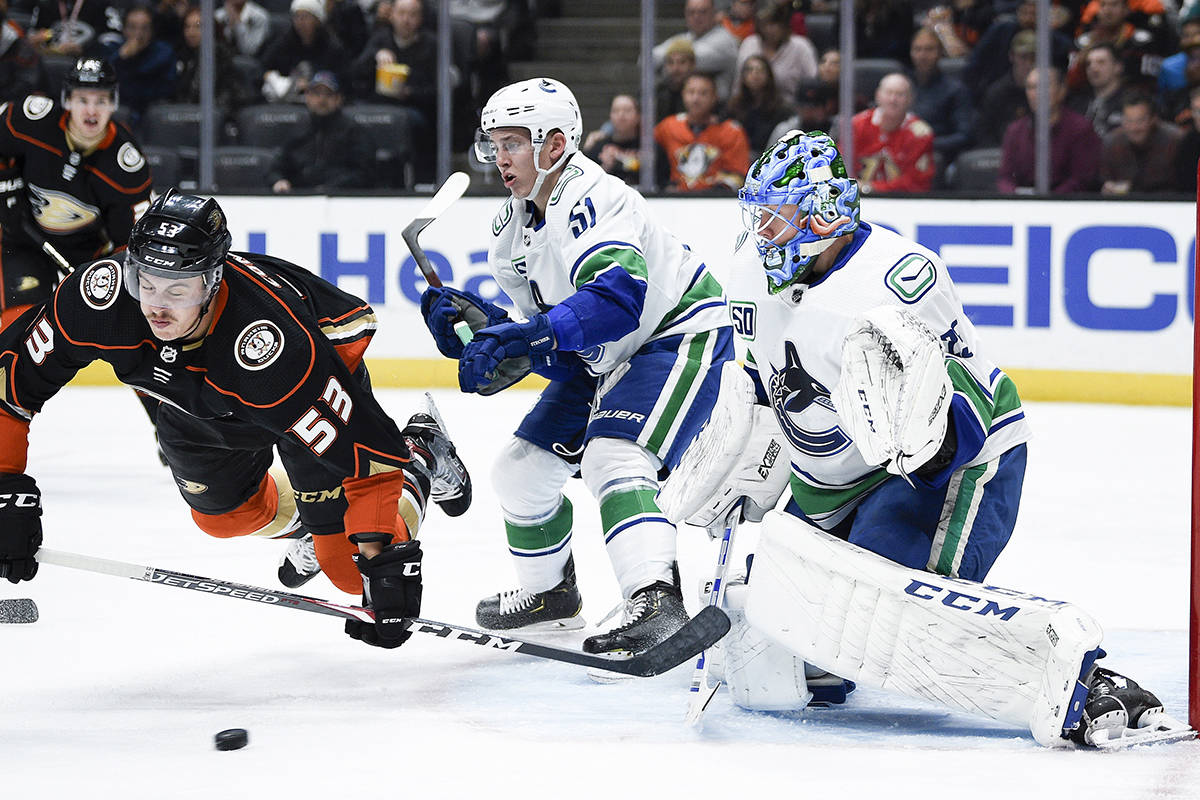 Anaheim Ducks left wing Max Comtois, left, falls to the ice while working for position against Vancouver Canucks defenceman Troy Stecher, centre, as Jacob Markstrom guards the goal during the second period of an NHL hockey game in Anaheim, Calif., Friday, Nov. 1, 2019. (AP Photo/Kelvin Kuo)