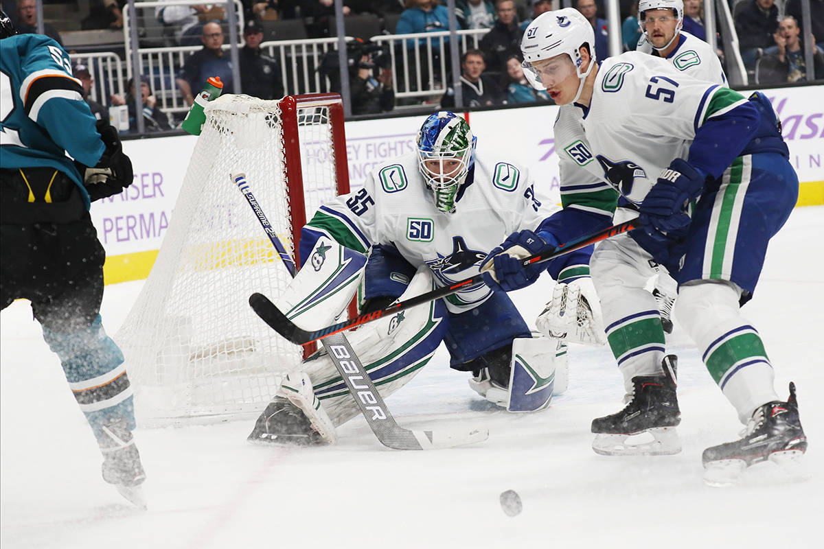 Vancouver Canucks goaltender Thatcher Demko (35) eyes the puck as his team plays the San Jose Sharks during the first period of an NHL hockey game Saturday, Nov. 2, 2019, in San Jose, Calif. (AP Photo/Jim Gensheimer)