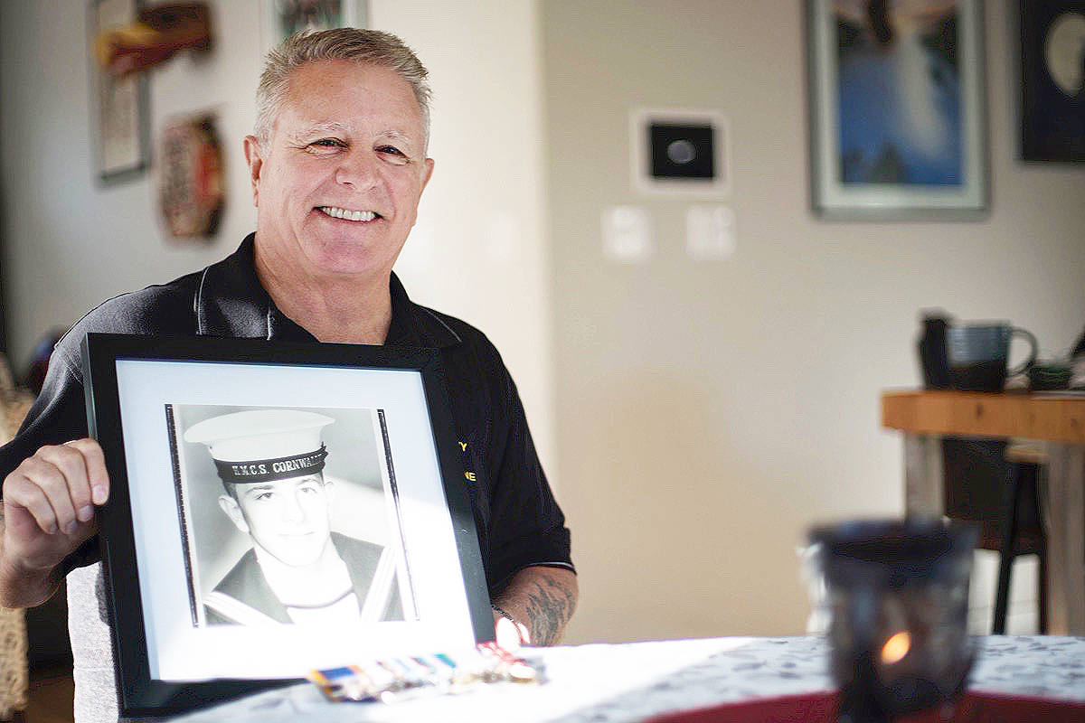 Ernie Peaker with a photograph of himself when he first joined the Navy at age 17 - Cloe Logan photo