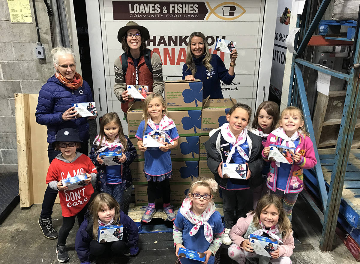 Girl Guide leaders Linda Jack, back left, Cassandra Jack and Sarah Pachkowsky and the Cedar Sparks unit delivers 20 cases of cookies to Loaves and Fishes Community Food Bank on Monday night. (Photo submitted)