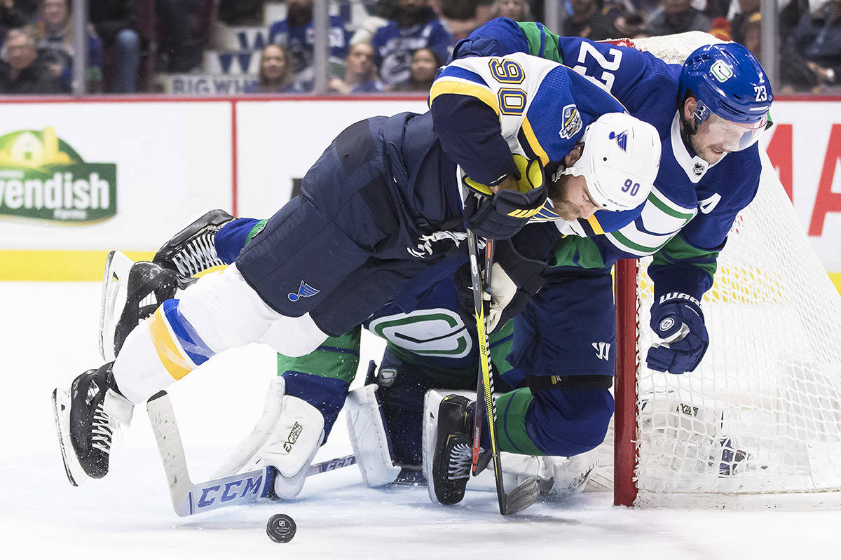 Vancouver Canucks' Alexander Edler (23), of Sweden, hauls down St. Louis Blues' Ryan O'Reilly (90) in front of goalie Jacob Markstrom, back, of Sweden, during the third period of an NHL hockey game in Vancouver, on Tuesday November 5, 2019. THE CANADIAN PRESS/Darryl Dyck