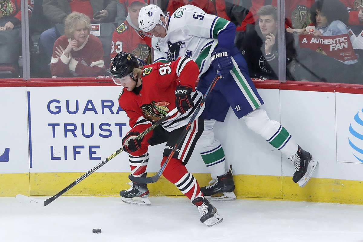 Chicago Blackhawks' Alex Nylander (92) keeps Vancouver Canucks' Tyler Myers away from the puck during the first period of an NHL hockey game Thursday, Nov. 7, 2019, in Chicago. (AP Photo/Charles Rex Arbogast)
