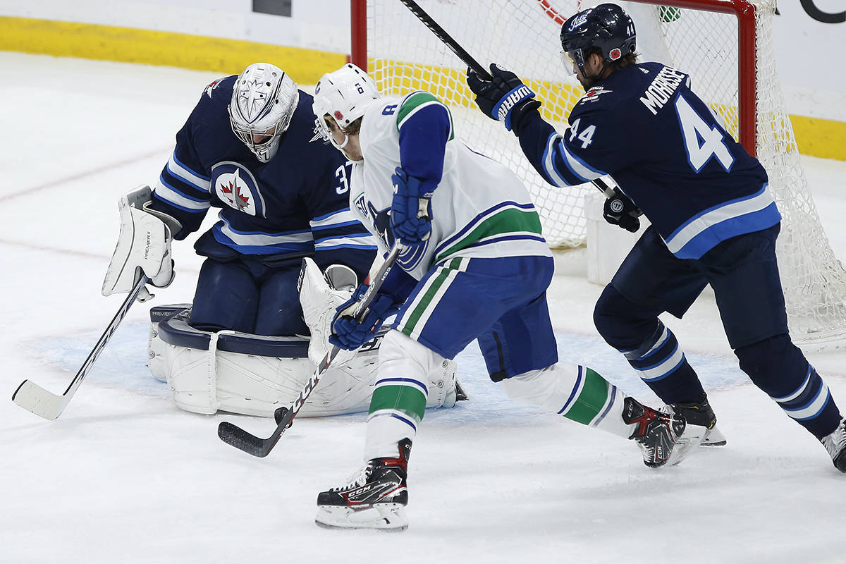 Winnipeg Jets goaltender Connor Hellebuyck (37) makes a save on Vancouver Canucks' Brock Boeser (6) as Josh Morrissey (44) defends during first period NHL action in Winnipeg, Friday, Nov. 8, 2019. THE CANADIAN PRESS/John Woods