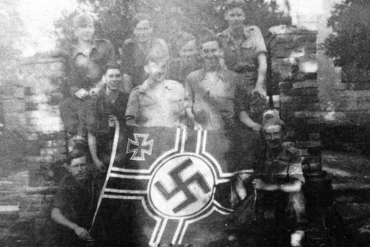 Corporal Reginald Wise (middle) stands with his fellow No. 40 Commando Royal Marines in Albania in 1944 shortly after capturing a Nazi flag. (Photo courtesy Reginald Wise)
