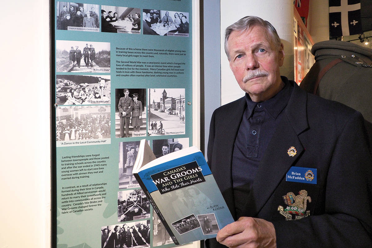 Brian McFadden, vice-president of Vancouver Island Military Museum, holds a copy of Canada's War Grooms and the Girls Who Stole Their Hearts, a book by Judy Kozar which helped form the basis for the museum's new exhibit about servicemen from overseas who found love while training in Canada and made their lives here after the Second World War. (CHRIS BUSH/The News Bulletin)