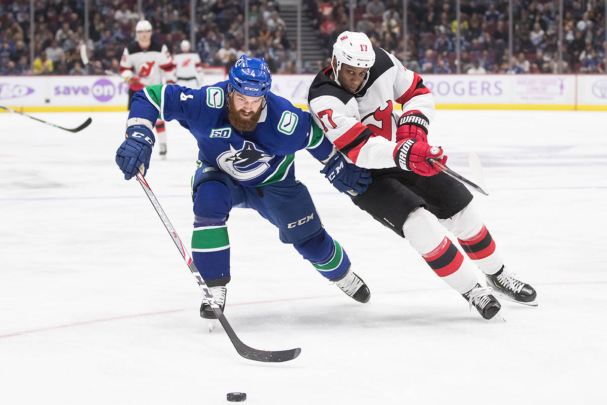 Vancouver Canucks' Jordie Benn, left, and New Jersey Devils' Wayne Simmonds vie for the puck during the first period of an NHL hockey game in Vancouver, on Sunday November 10, 2019. THE CANADIAN PRESS/Darryl Dyck