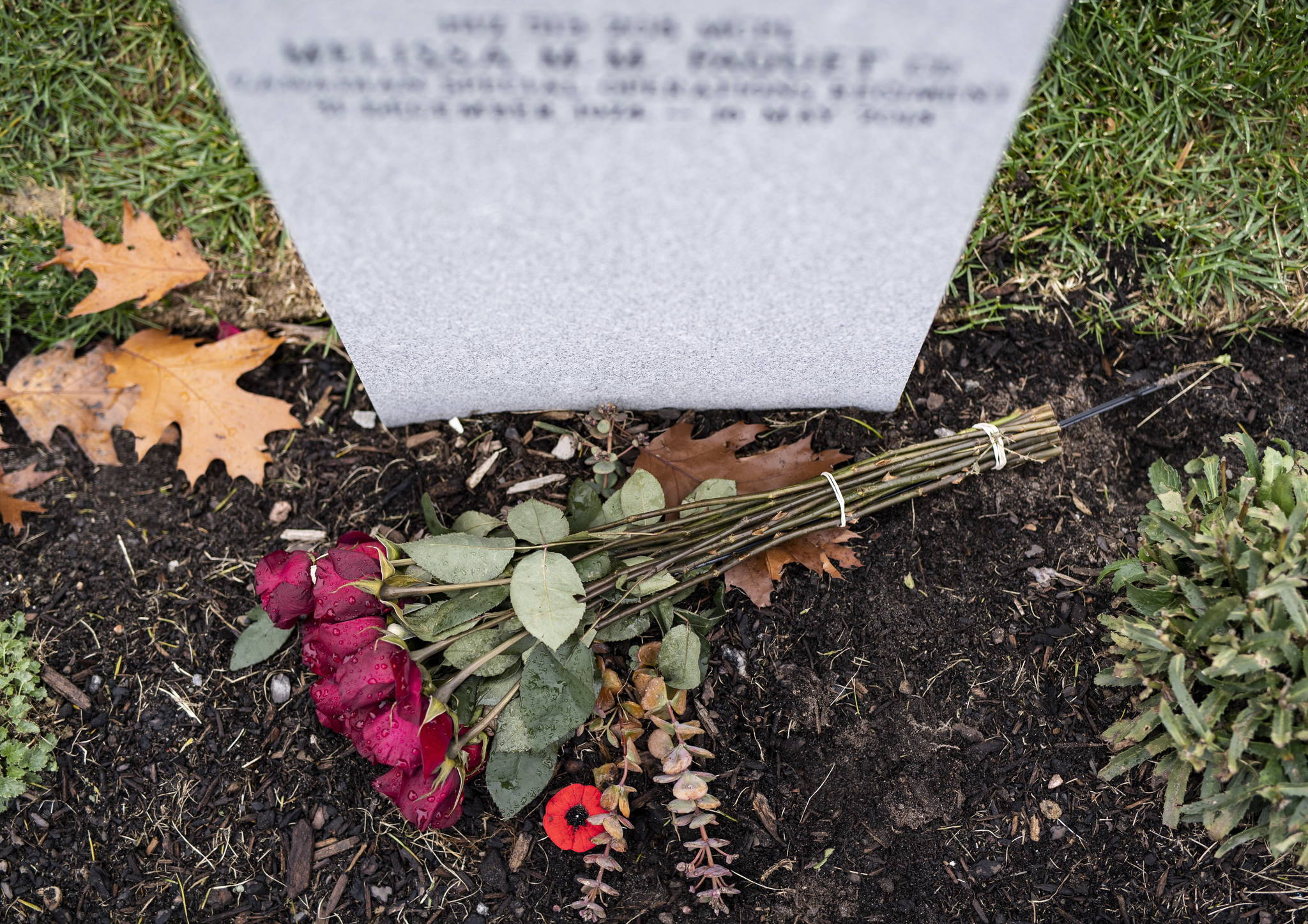 A bouquet of roses and a poppy lie at the foot of a grave at the National Military Cemetery at Beechwood Cemetery in Ottawa on the day before Remembrance Day, Sunday, Nov. 10, 2019. THE CANADIAN PRESS/Justin Tang
