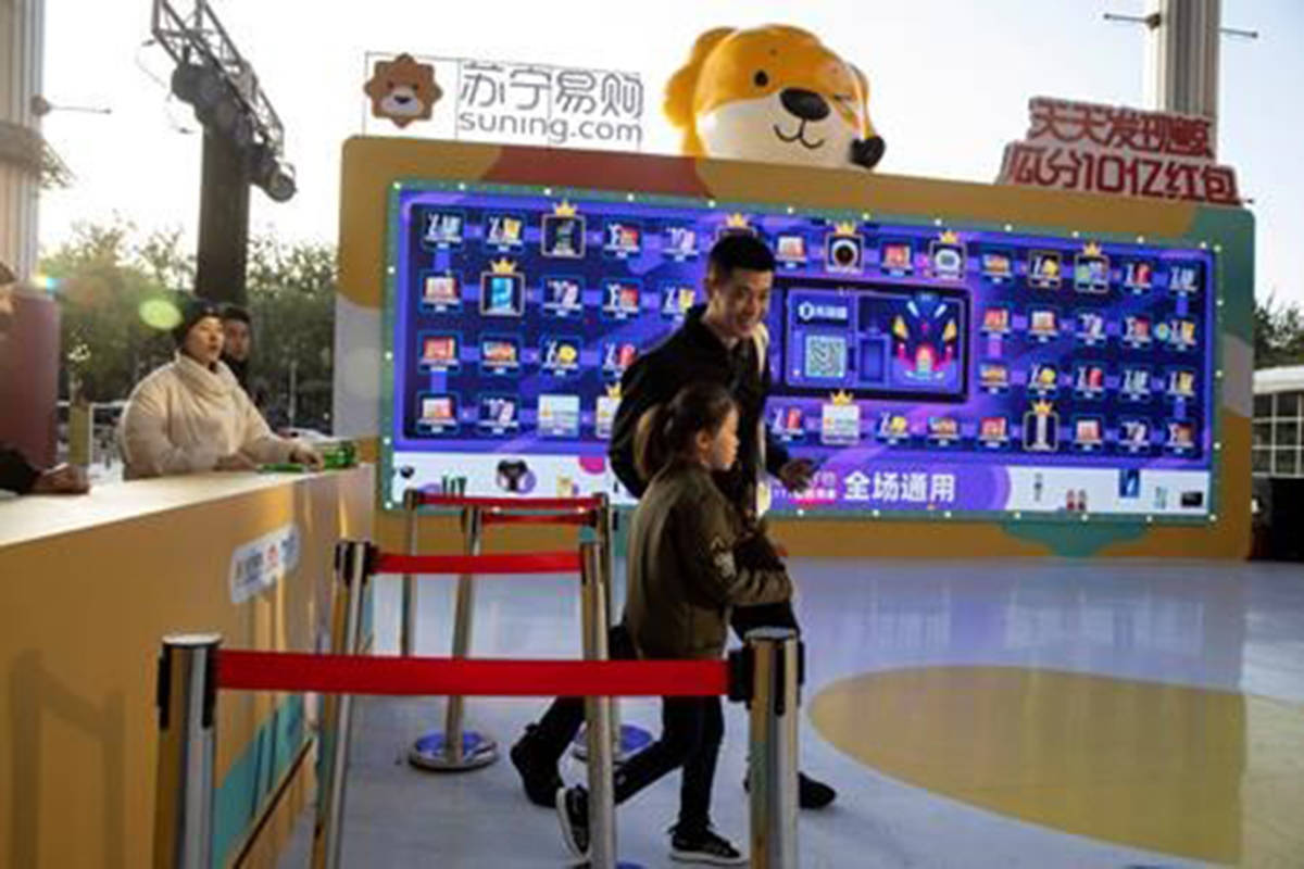 In this photo taken Sunday, Nov. 10, 2019, shoppers react after taking part in a promotion ahead of Nov. 11 Singles day in Beijing. Chinese online shoppers hunt bargains on Singles Day, a holiday invented in the 1990s that has become the world's busiest day for online commerce. (AP Photo/Ng Han Guan)