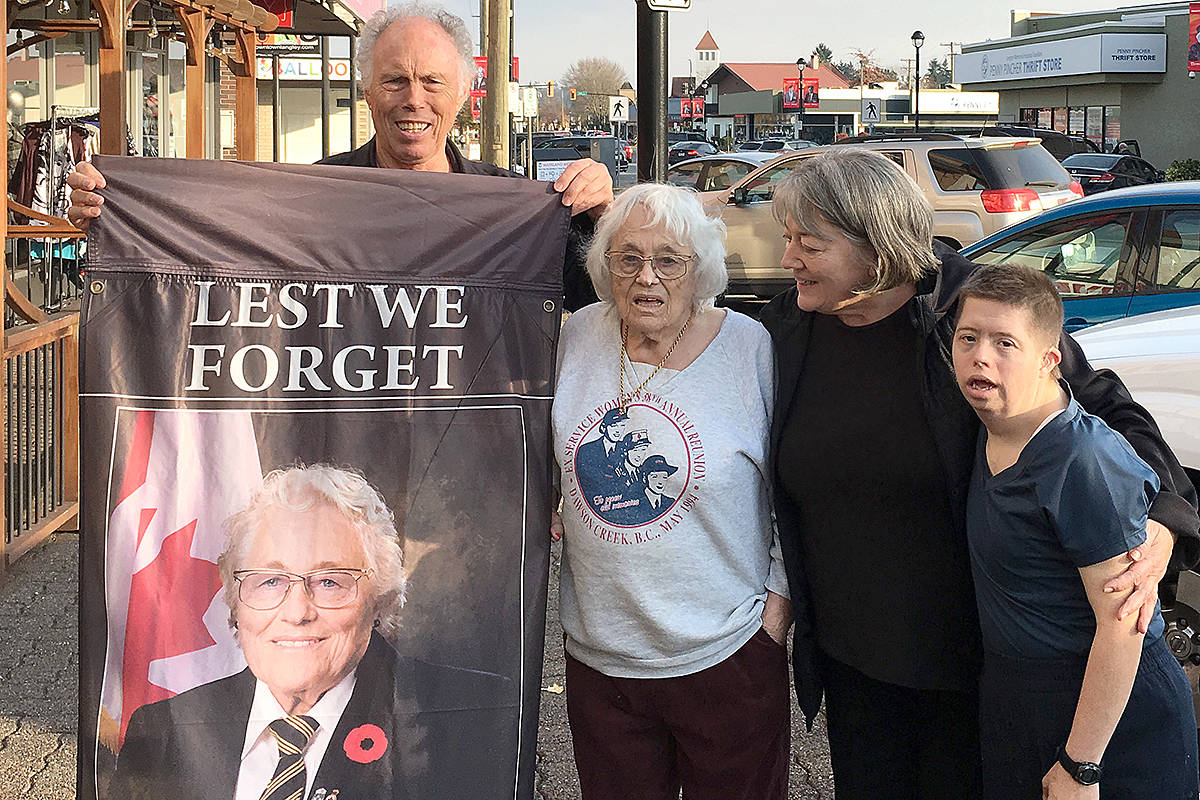 Marjorie Mazerall and her family picked up the old street banner gifted to her by the Downtown Langley Business Association. A new banner, boasting her likeness, now hangs on the one-way street. (Downtown Langley Business Association/Special to the Langley Advance Times)