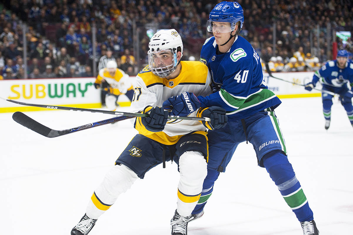 Vancouver Canucks centre Elias Pettersson (40) fights for control of the puck with Nashville Predators defenceman Dante Fabbro (57) during first period NHL action in Vancouver, Tuesday, Nov. 12, 2019. THE CANADIAN PRESS/Jonathan Hayward