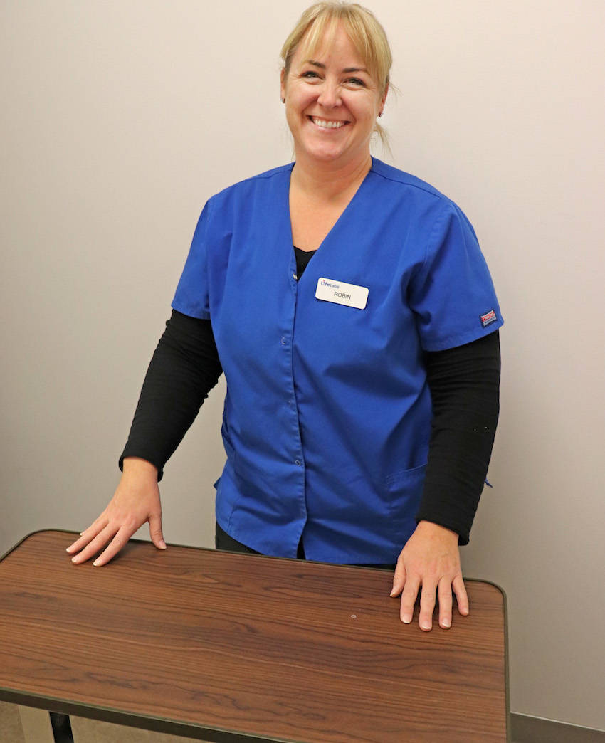 "Pambrun makes use of an adjustable table which she can ""slide right up to patients"" located anywhere inside the centre, if patients are not able to access their a phlebotomy cubicles. (Sarah Grochowski photo)"