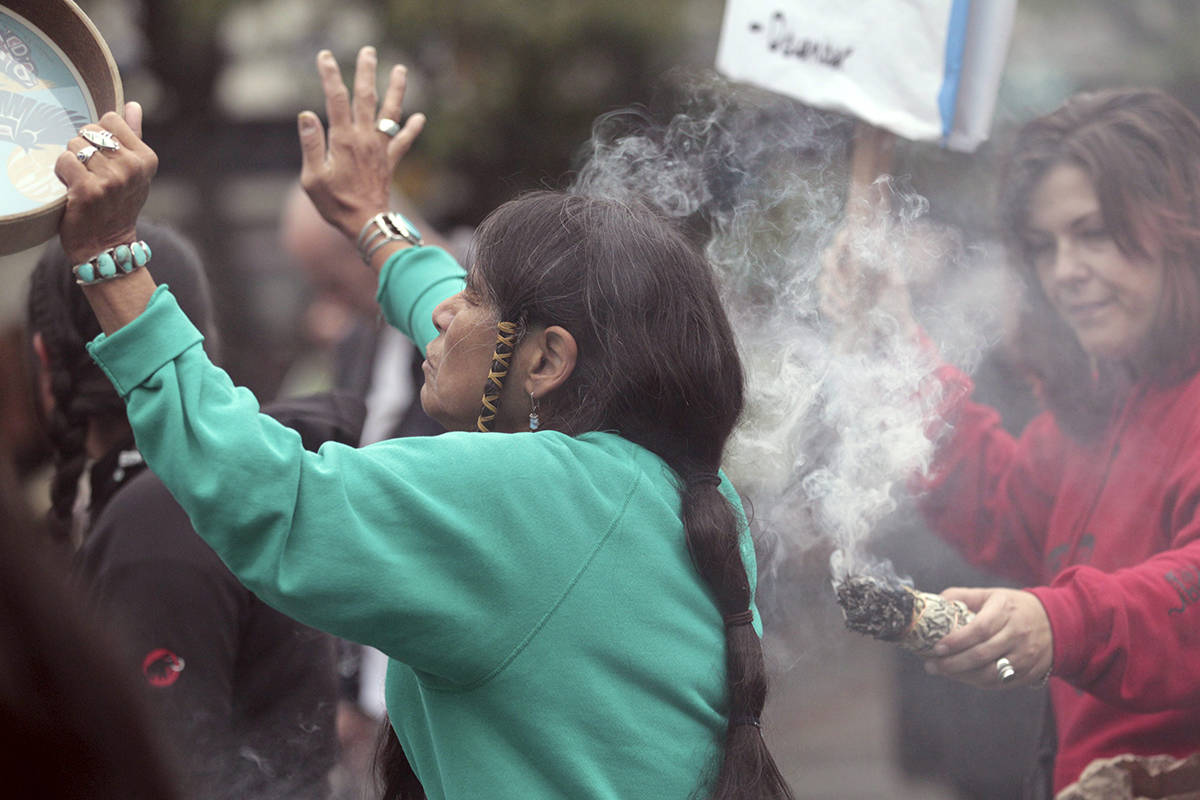 "Ferntree, of Duncan, British Columbia, a member of the Cowichan Tribes, holds her hand up as she partakes in a smudging ceremony as smoke from a smoldering bundle of dried sweetgrass is directed toward her during a Native American protest against Columbus Day, Monday, Oct. 10, 2011, in Seattle. The fourth annual protest by the Oldgrowth Alliance included leaders and youth from Native American and Alaska Native communities speaking out against the annual holiday honoring Christopher Columbus' arrival in the Americas. Protest organizers say that Columbus could not have ""discovered"" a western hemisphere already inhabited by about 100 million people. (AP Photo/Elaine Thompson)"