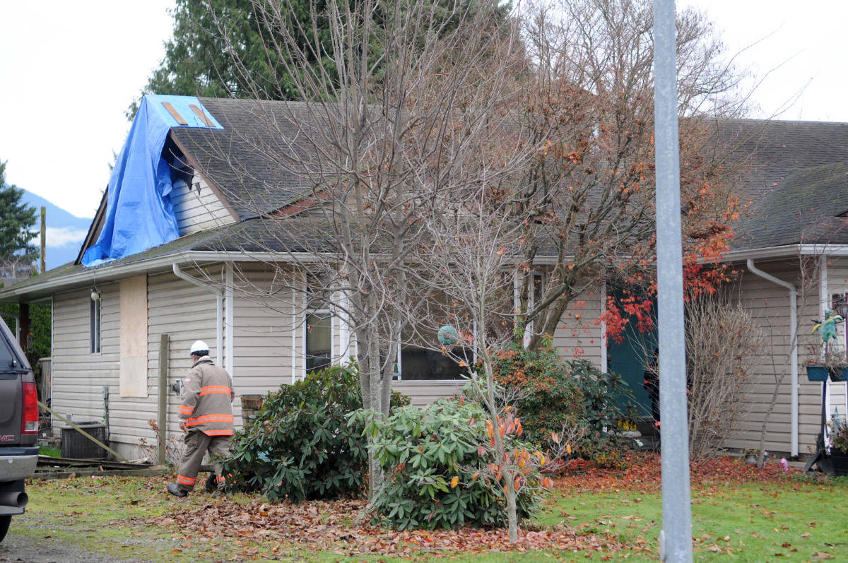 A firefighter walks around to the back of a house on Ashwell Road in Chilliwack where a fire broke out on Saturday night. (Jenna Hauck/ The Progress)