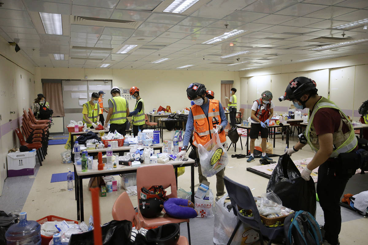 Volunteer medical workers gather up supplies inside Hong Kong Polytechnic University in Hong Kong, Tuesday, Nov. 19, 2019. About 100 anti-government protesters remained holed up at a Hong Kong university Tuesday, their choices dwindling along with their food supplies as they braced for the endgame in a police siege of the campus that entered its third day. (AP Photo/Achmad Ibrahim)