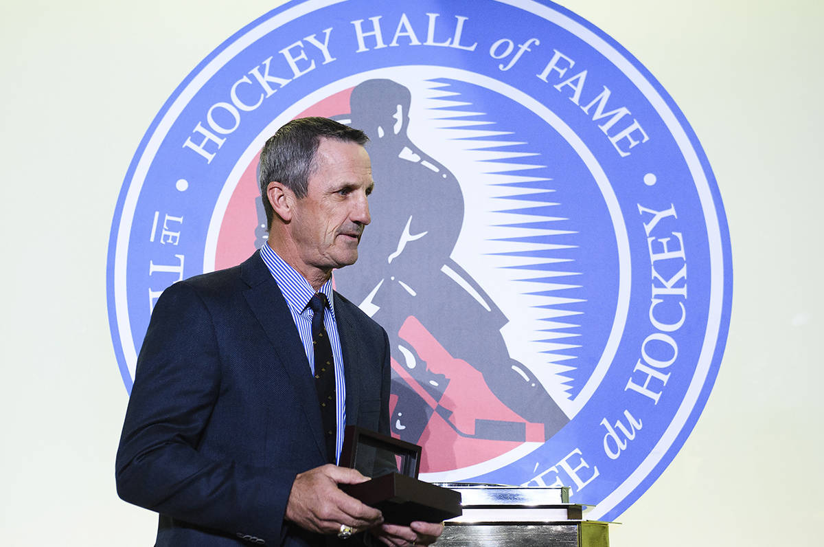 Hockey Hall of Fame inductee Guy Carbonneau walks on stage with his ring in Toronto on Friday, November 15, 2019. THE CANADIAN PRESS/Nathan Denette