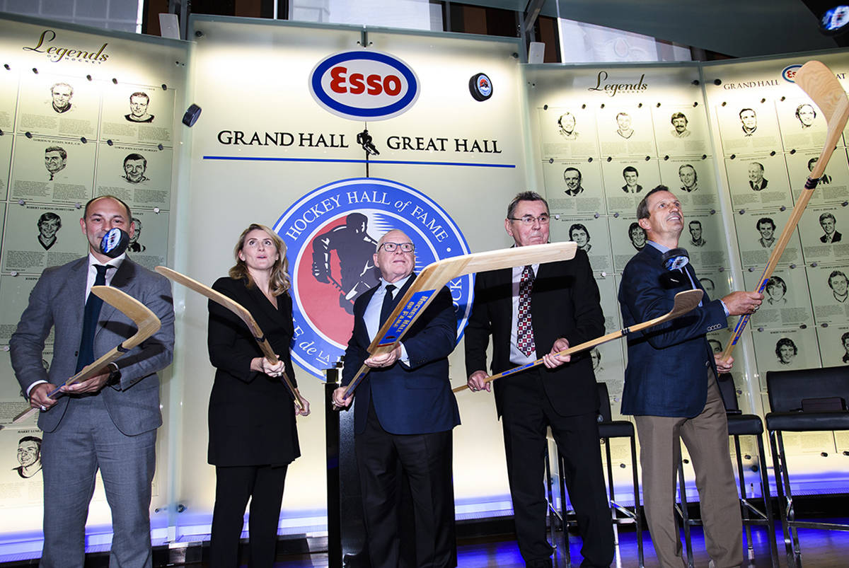 Hockey Hall of Fame inductees Sergei Zubov, (left to right), Hayley Wickenheiser, Jim Rutherford, Vaclav Nedomansky and Guy Carbonneau flip pucks in the air during a ceremony in Toronto on Friday, November 15, 2019. THE CANADIAN PRESS/Nathan Denette