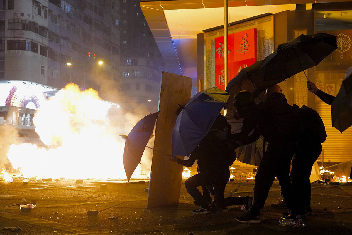Protesters take cover with umbrellas from tear gas canister in the Kowloon area of Hong Kong, on Monday, Nov. 18. As night fell in Hong Kong, police tightened a siege at a university campus as hundreds of anti-government protesters trapped inside sought to escape. (AP Photo/Vincent Yu)