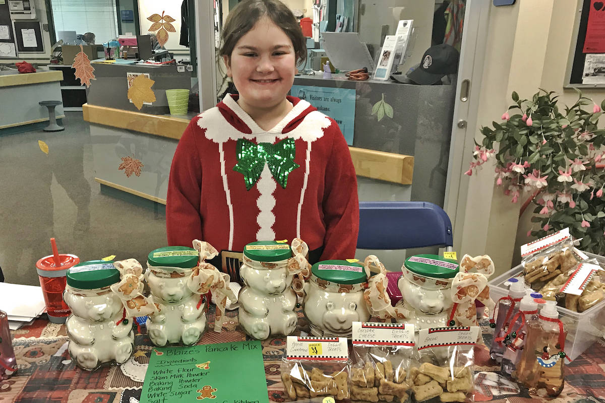 Grade 3 student and return seller Blaize wore a Mrs. Claus sweater while she sold her wares to passersby. (Sarah Grochowski photo)