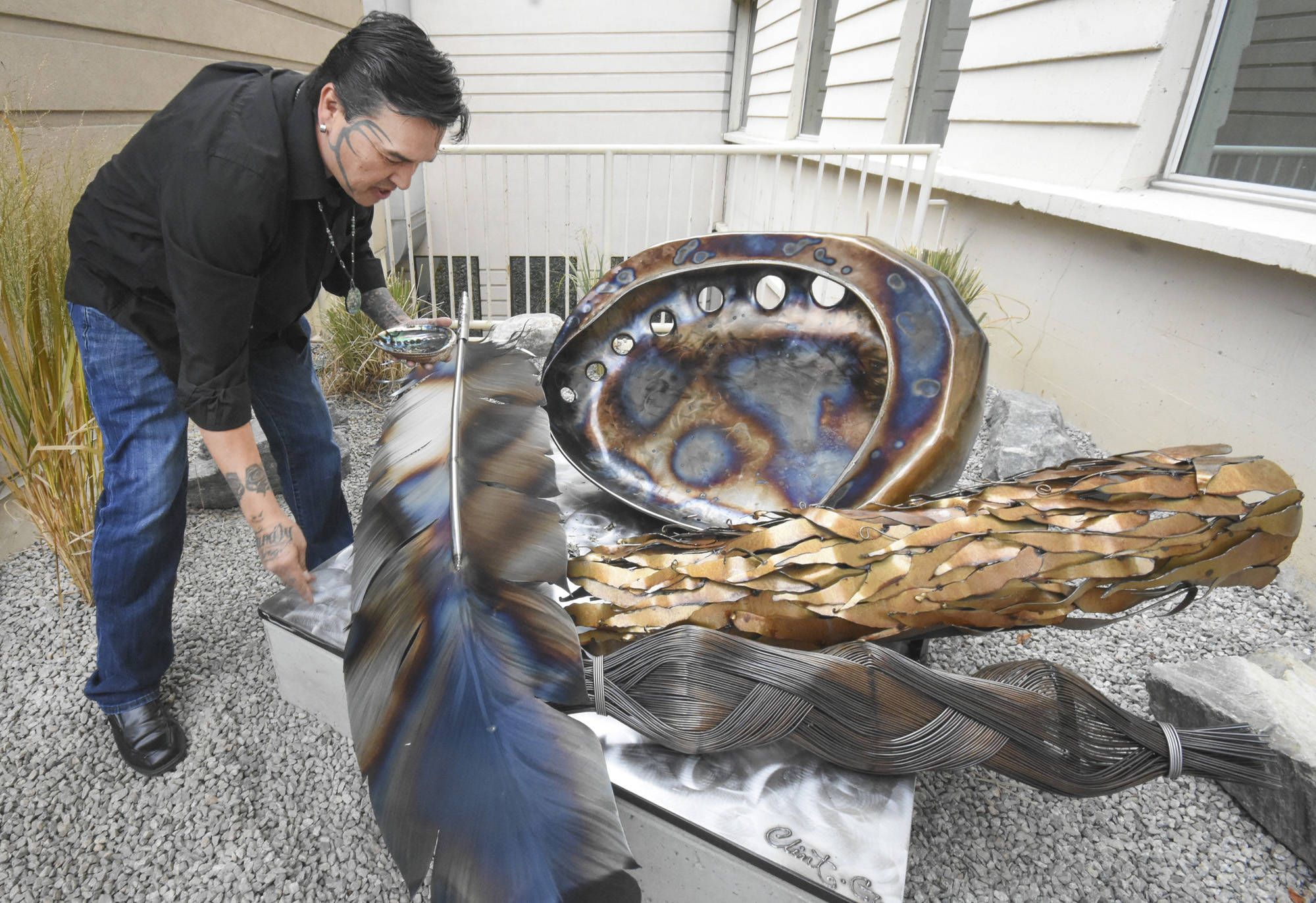 An artist sprinkles ashes from a smudging ceremony on his sculpture unveiled at Penticton Regional Hospital in 2018. (Mark Brett/Western News)