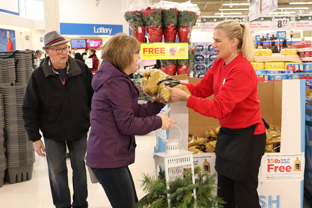 Langley Superstore employee, Michele Cozicar, handed customers their complimentary bag of potatoes on Friday during a customer appreciation event. (Joti Grewal/Langley Advance Times)