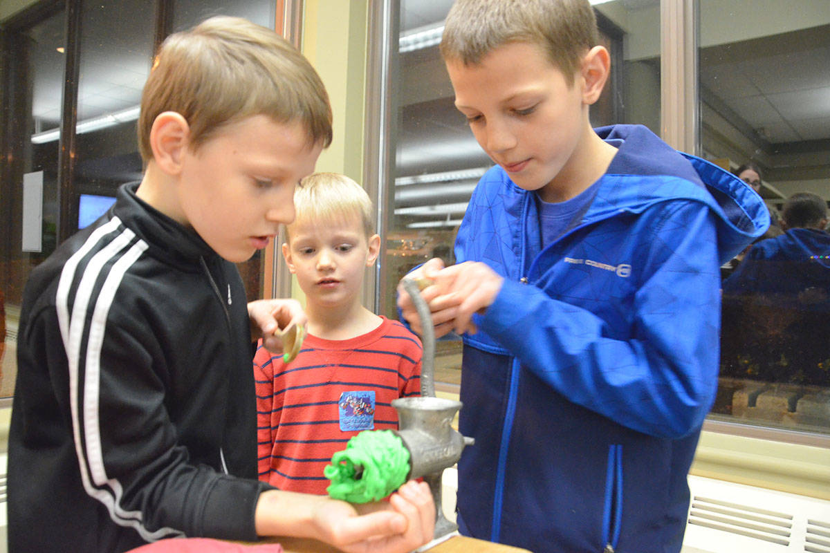 Retro Tech Tryout on Thursday allowed the public to try out technology from bygone days. While Micah Vandergriendt looked on, his brothers Eli and Josiah tried out a vintage food grinder, using plasticine. (Heather Colpitts/Langley Advance Times)