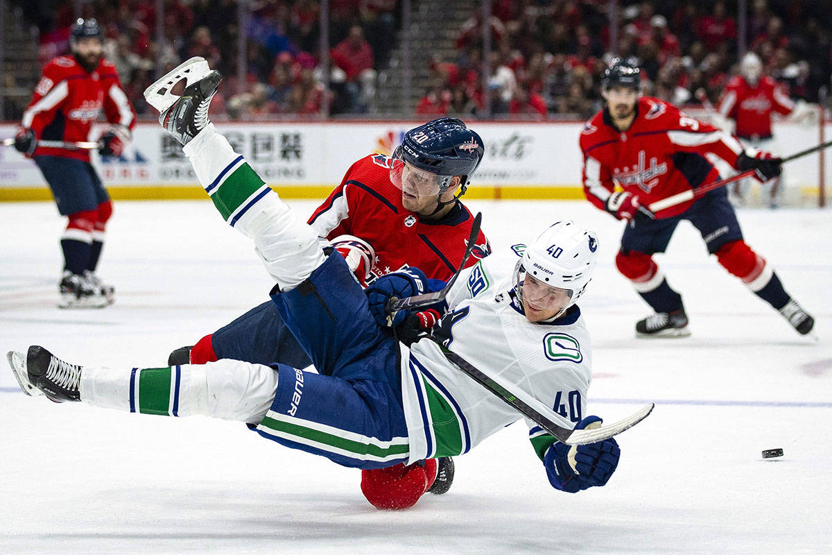 Washington Capitals centre Lars Eller (20), from Denmark, collides with Vancouver Canucks centre Elias Pettersson (40) from Sweden, during the second period of an NHL hockey game, Saturday, Nov. 23, 2019, in Washington. (AP Photo/Al Drago)