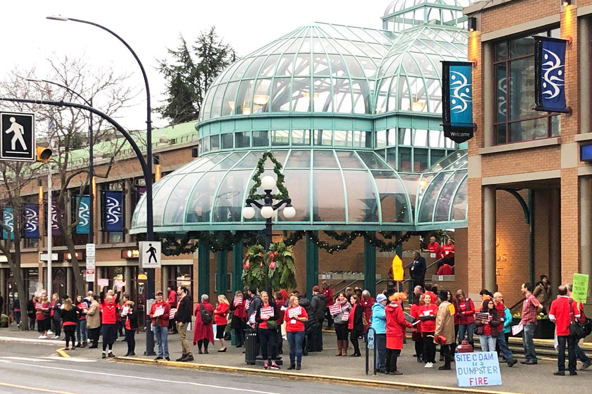 BCTF members, all dressed in red, lined Douglas Street to hand out leaflets, wave their signs and talk with residents and BC NDP Convention attendees on Saturday. (Devon Bidal/News Staff)