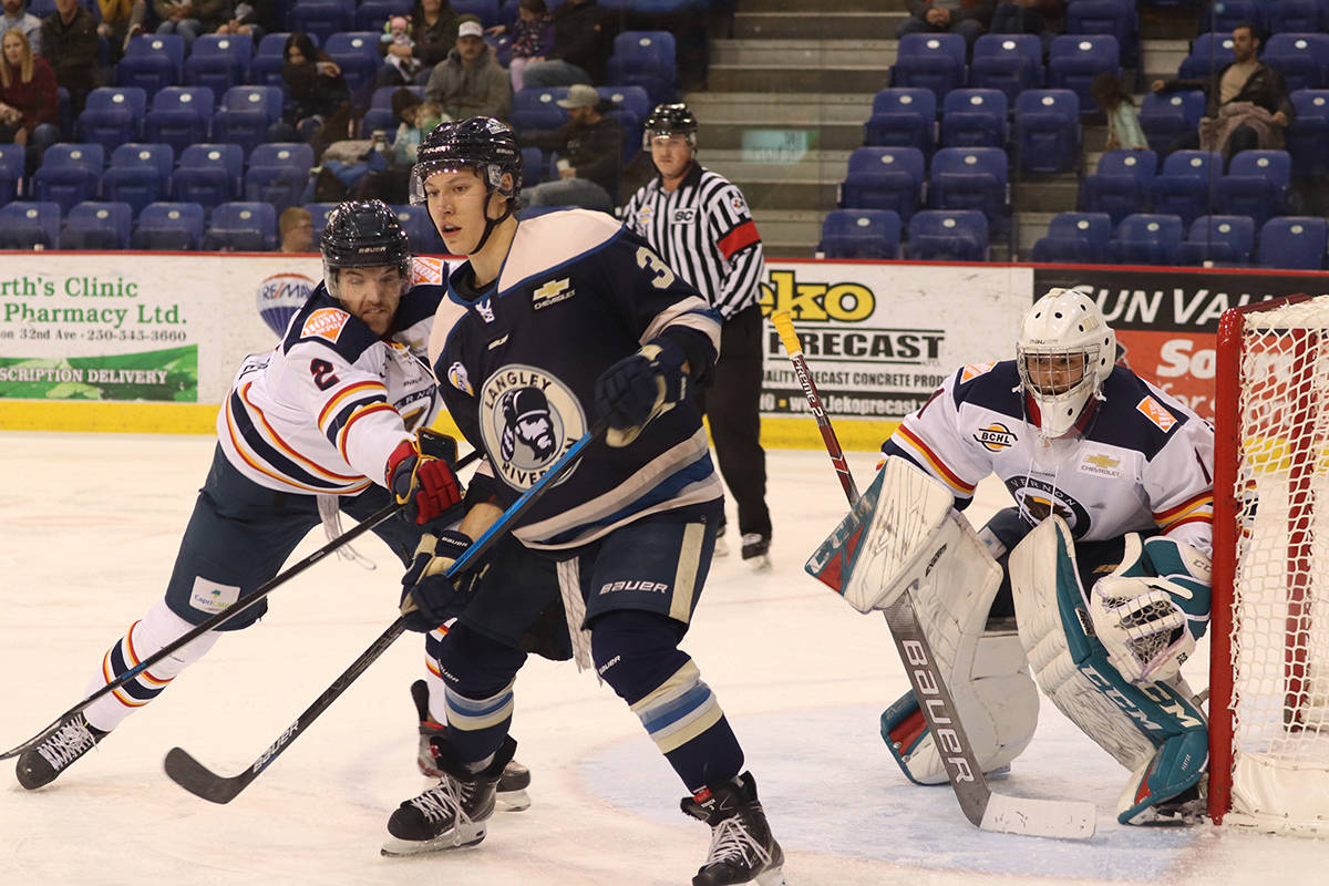 Vernon Vipers defenceman Landon Fuller (left) puts some wood on Langley Rivermen forward Colten Kovich in front of Vipers goalie Jack Porter, Jr. during the Rivermen's 3-1 B.C. Hockey League win Saturday, Nov. 23, in Vernon. (Roger Knox - Black Press)