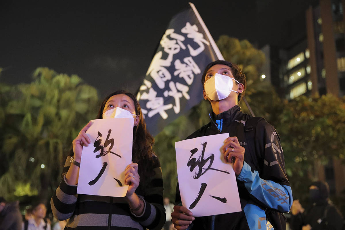 "Protesters hold placards baring the words ""Release People"", as they gather near the Polytechnic University in Hong Kong, Monday, Nov. 25, 2019. Hong Kong's pro-democracy opposition won a stunning landslide victory in weekend local elections in a clear rebuke to city leader Carrie Lam over her handling of violent protests that have divided the semi-autonomous Chinese territory. (AP Photo/Kin Cheung)"