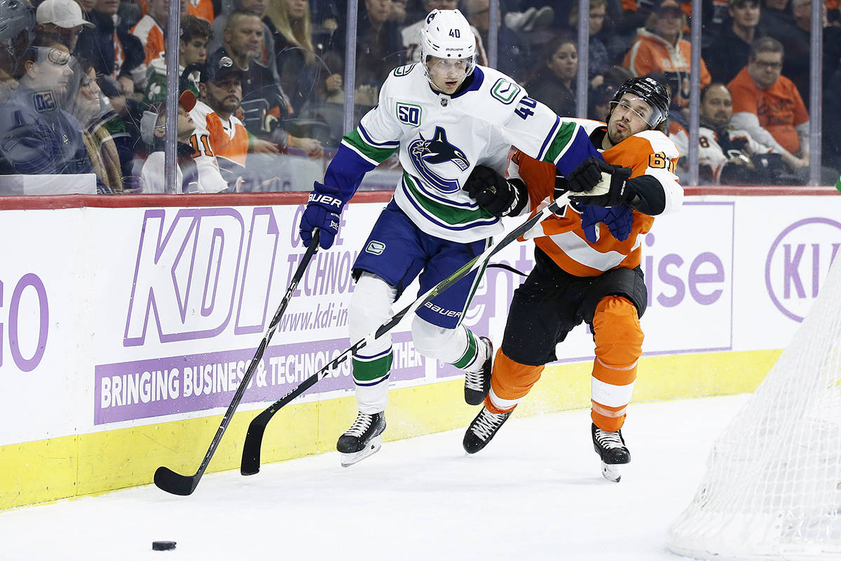 Vancouver Canucks' Elias Pettersson (40) and Philadelphia Flyers' Justin Braun (61) battle for the puck during the first period of an NHL hockey game, Monday, Nov. 25, 2019, in Philadelphia. (AP Photo/Matt Slocum)