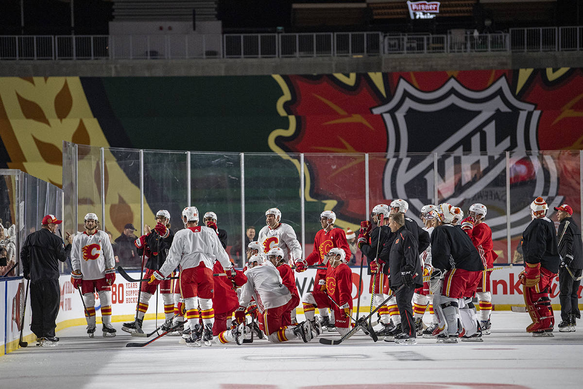 Calgary Flames head coach Bill Peters, left, speaks to players during practice for the NHL Heritage Classic outdoor hockey game in Regina on Friday, October 25, 2019. THE CANADIAN PRESS/Liam Richards