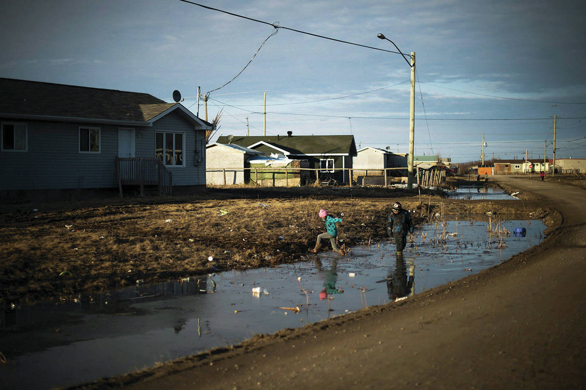 Indigenous children play in water-filled ditches in Attawapiskat, Ont. on April 19, 2016. Federal lawyers will be in court later this morning to argue the government's appeal of a Canadian Human Rights Tribunal ruling that ordered Ottawa to pay billions of dollars in compensation to First Nations children and their families. THE CANADIAN PRESS/Nathan Denette