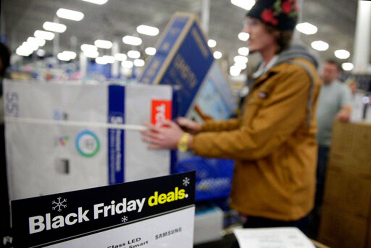 In this Nov. 22, 2018, file photo people wait in line to buy televisions as they shop during an early Black Friday sale at a Best Buy store on Thanksgiving Day in Overland Park, Kan. Black Friday is Nov. 29, 2019. (AP Photo/Charlie Riedel, File)