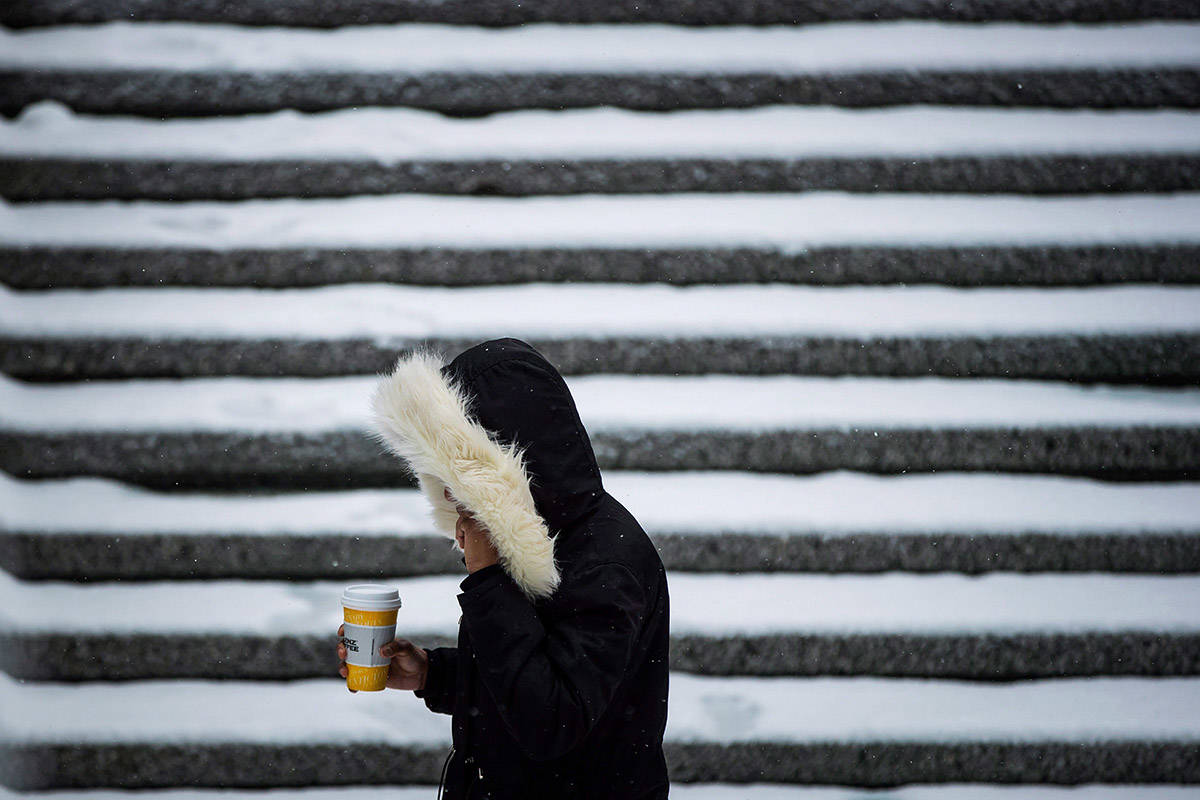 A bitter cold snap gripping much of British Columbia's south coast, central and northeast regions is being compounded by strong winds in some southern areas and snow in the central Interior. A woman walks through a snow covered plaza in downtown Vancouver, Friday, Feb. 23, 2018. THE CANADIAN PRESS/Darryl Dyck