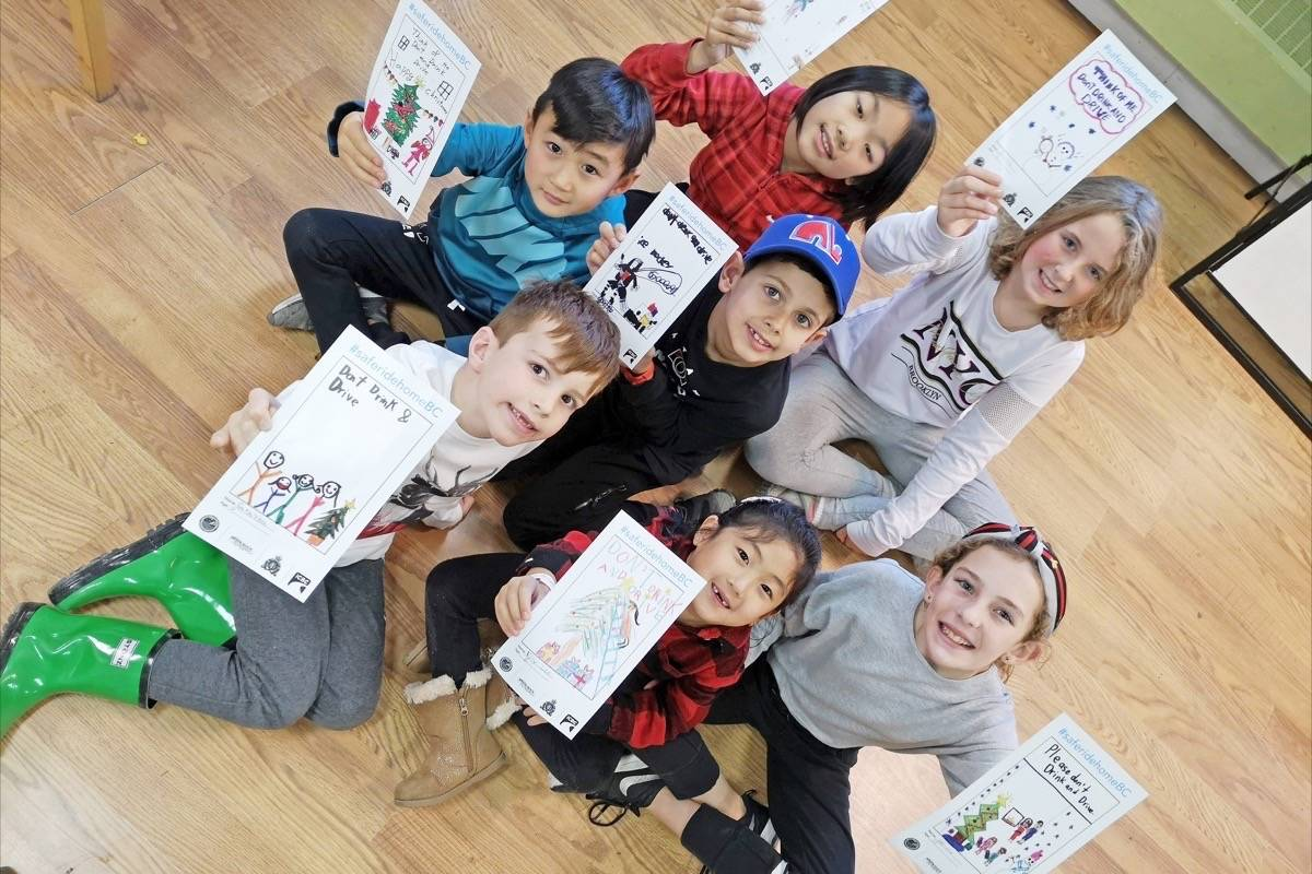 Grayson Sears, Joshua Lee, Chelsea Huang, Alexandra Cox, Adriana Dalgetty, Elly Lee and Matteo McLaughlin show some of the 'Think of Me' sticker designs, prior to helping affix them to a stack of brown-sleeve bags. (Tracy Holmes photo)
