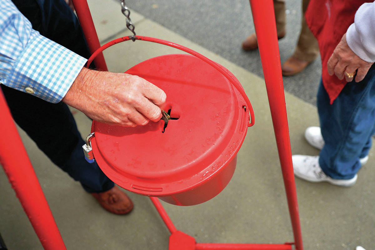 In this Nov. 9, 2018, file photo money gets dropped into the kettle during the Annual Salvation Army Red Kettle and Angel Tree Kick Off outside the Hobby Lobby store in Augusta, Ga. Canada's Salvation Army is testing out a new and faster way to allow cashless donations to its kettle stations via debit and credit card, making the process as quick and easy as dropping a toonie in the bubble. THE CANADIAN PRESS/AP-Michael Holahan/The Augusta Chronicle via AP, File