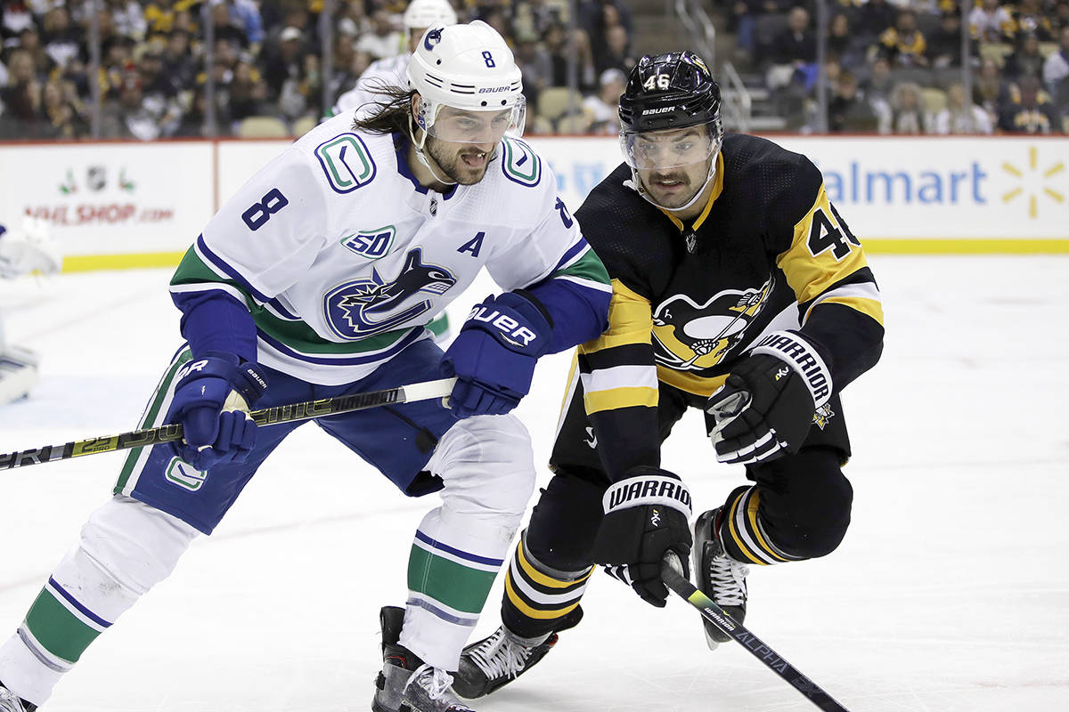 Vancouver Canucks' Christopher Tanev (8) and Pittsburgh Penguins' Zach Aston-Reese (46) skate into the corner after the puck during the second period of an NHL hockey game in Pittsburgh, Wednesday, Nov. 27, 2019. (AP Photo/Gene J. Puskar)