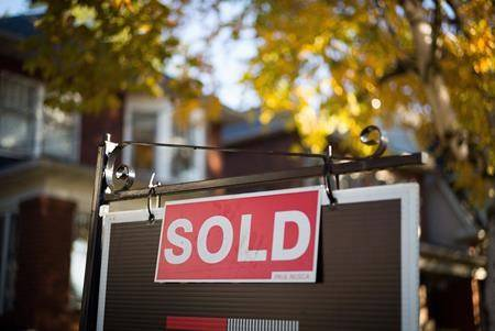 A real estate sold sign hangs in front of a west-end Toronto property. THE CANADIAN PRESS/Graeme Roy