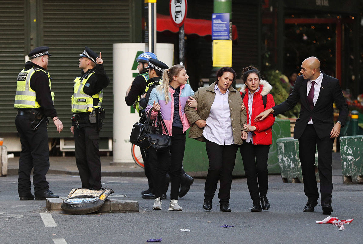 A woman, third right, is assisted after falling when Police evacuated people from Borough Market on the south side of London Bridge in London, Friday, Nov. 29, 2019. British police say several people have stabbed near to London Bridge, and a man has been detained. The news came after witnesses reported hearing gunshots in the area. (AP Photo/Frank Augstein)