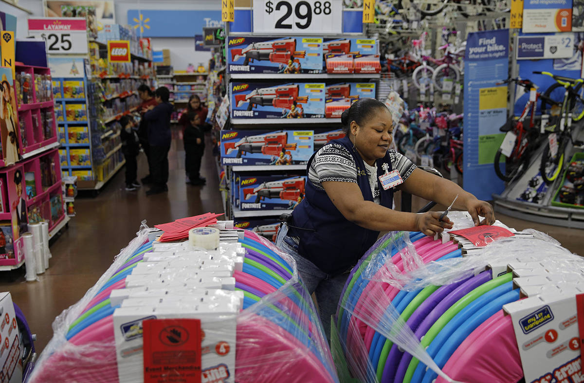 Balo Balogun labels items in preparation for a holiday sale at a Walmart Supercenter, Wednesday, Nov. 27, 2019, in Las Vegas. Black Friday once again kicks off the start of the holiday shopping season. But it will be the shortest season since 2013 because of Thanksgiving falling on the fourth Thursday. (AP Photo/John Locher)