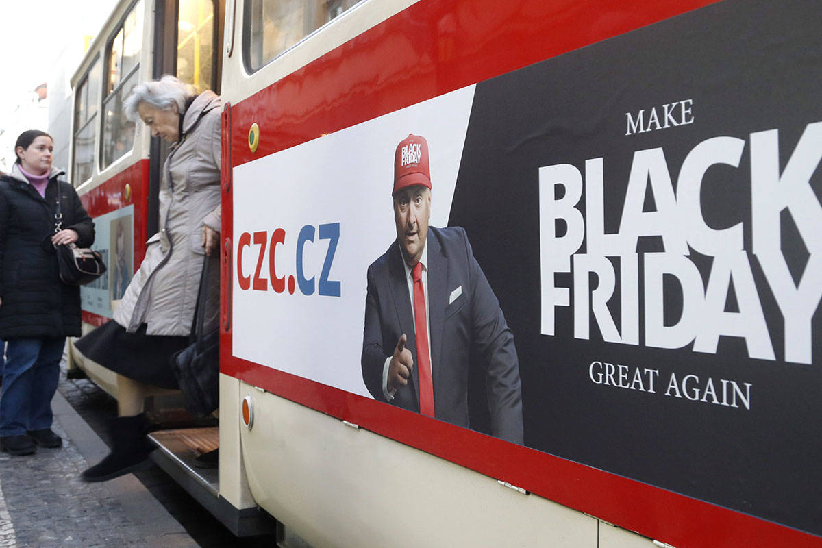 A woman gets off a tram advertising the Black Friday in Prague, Czech Republic, Thursday, Nov. 28, 2019. (AP Photo/Petr David Josek)