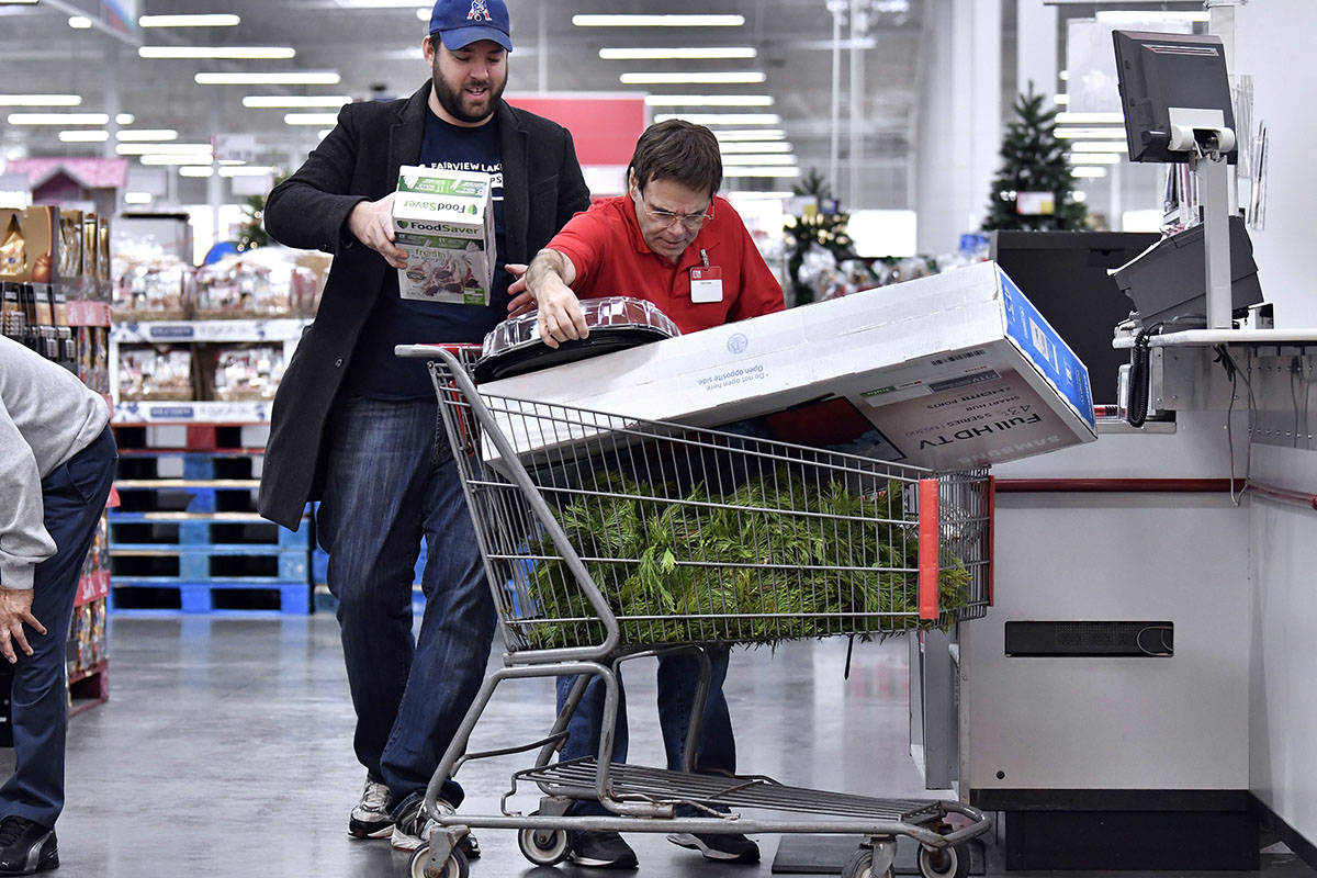 BJ's Wholesale Club member Andrew Pafaff of Southborough, Mass., reloads his cart as Team Member Victor Masciarelli rings him up during BJ's 11 Days of Black Friday Event on Friday, Nov. 29, 2019 in Northborough, Mass. (Josh Reynolds/AP Images for BJ's Wholesale Club)